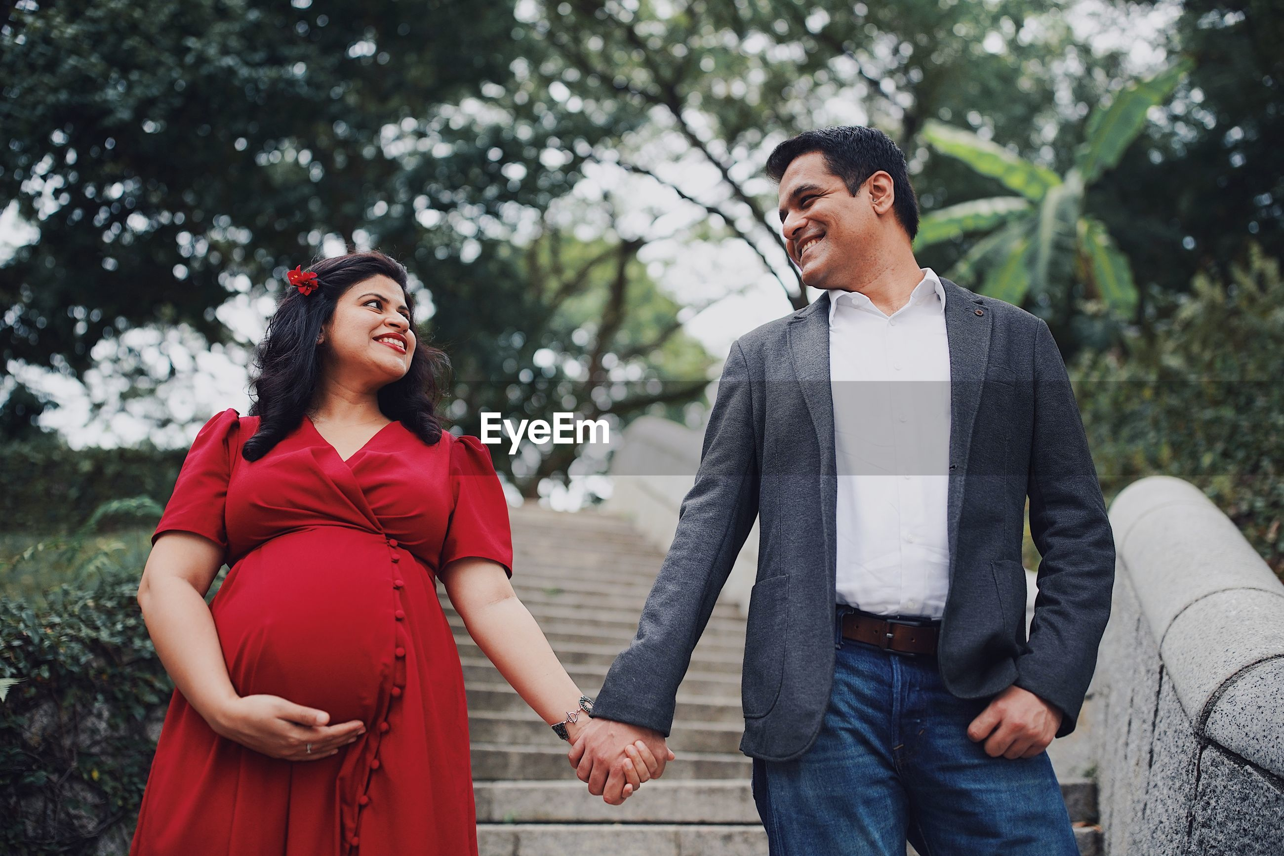 Pregnant couple holding hands while standing on steps