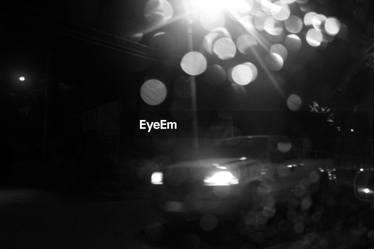 illuminated, night, lens flare, lighting equipment, glowing, no people, car, land vehicle, defocused, light beam, nightlife, spotlight, outdoors, city, close-up