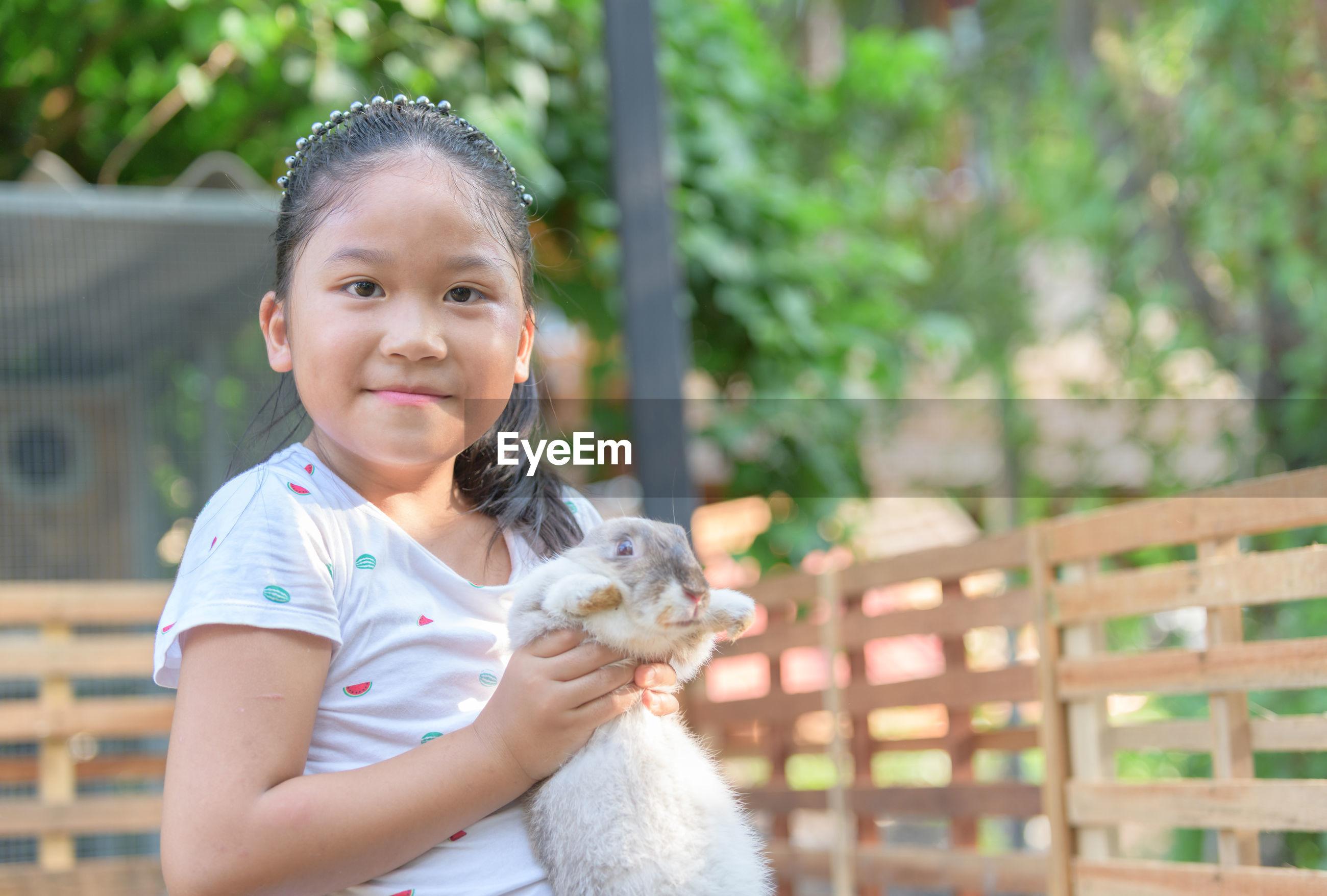 Portrait of girl holding rabbit