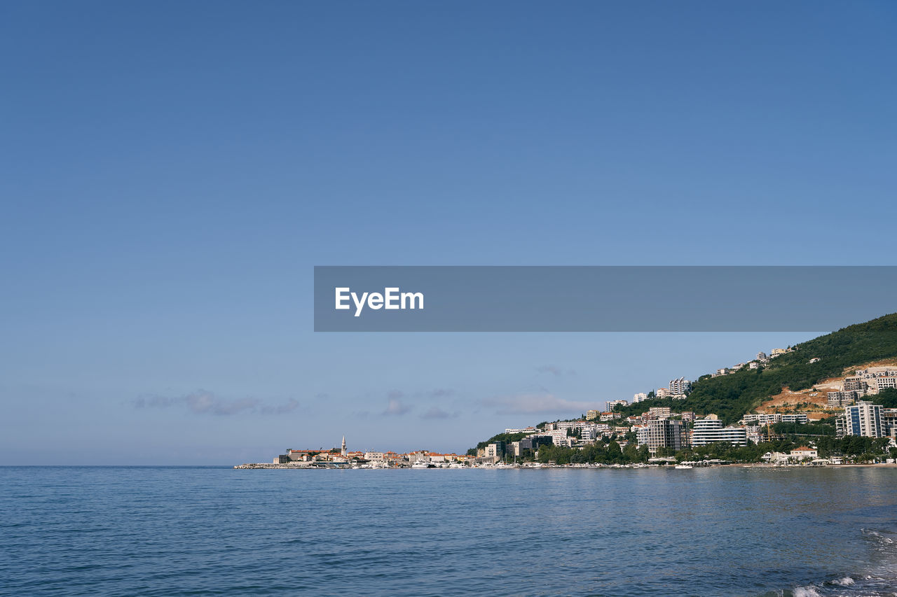 SCENIC VIEW OF SEA BY BUILDINGS AGAINST CLEAR SKY