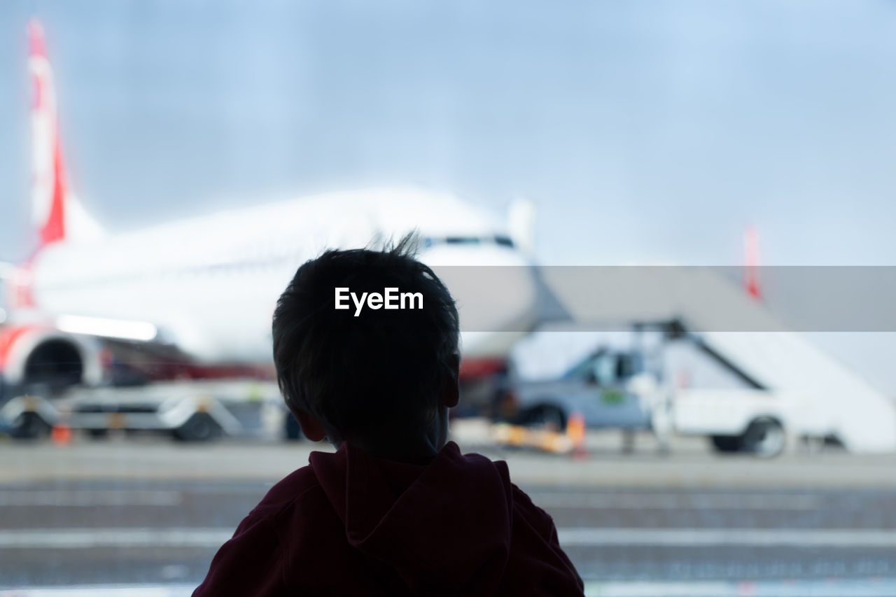 Rear View Of Boy Against Airplane At Airport