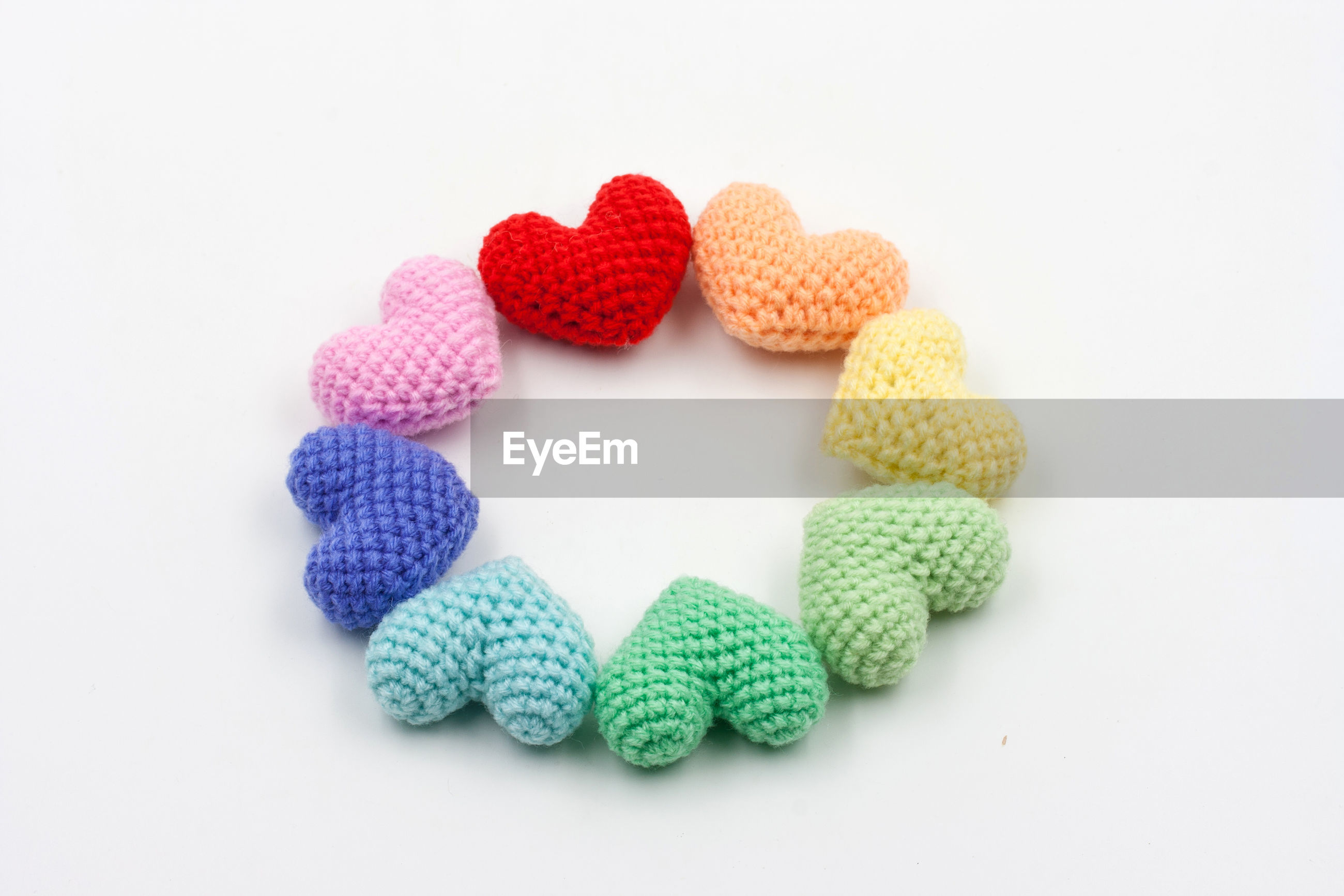 High angle view of woolen heart shapes on white background
