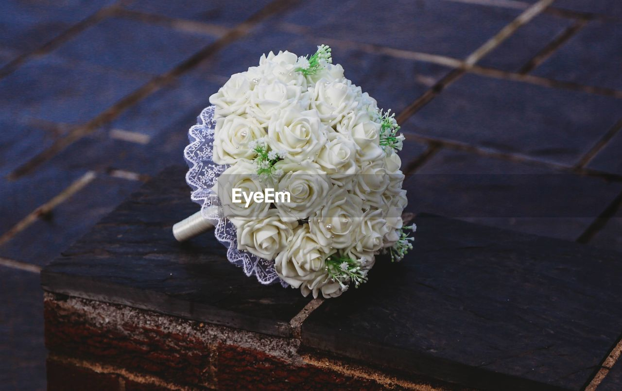 HIGH ANGLE VIEW OF ROSE BOUQUET ON WOOD