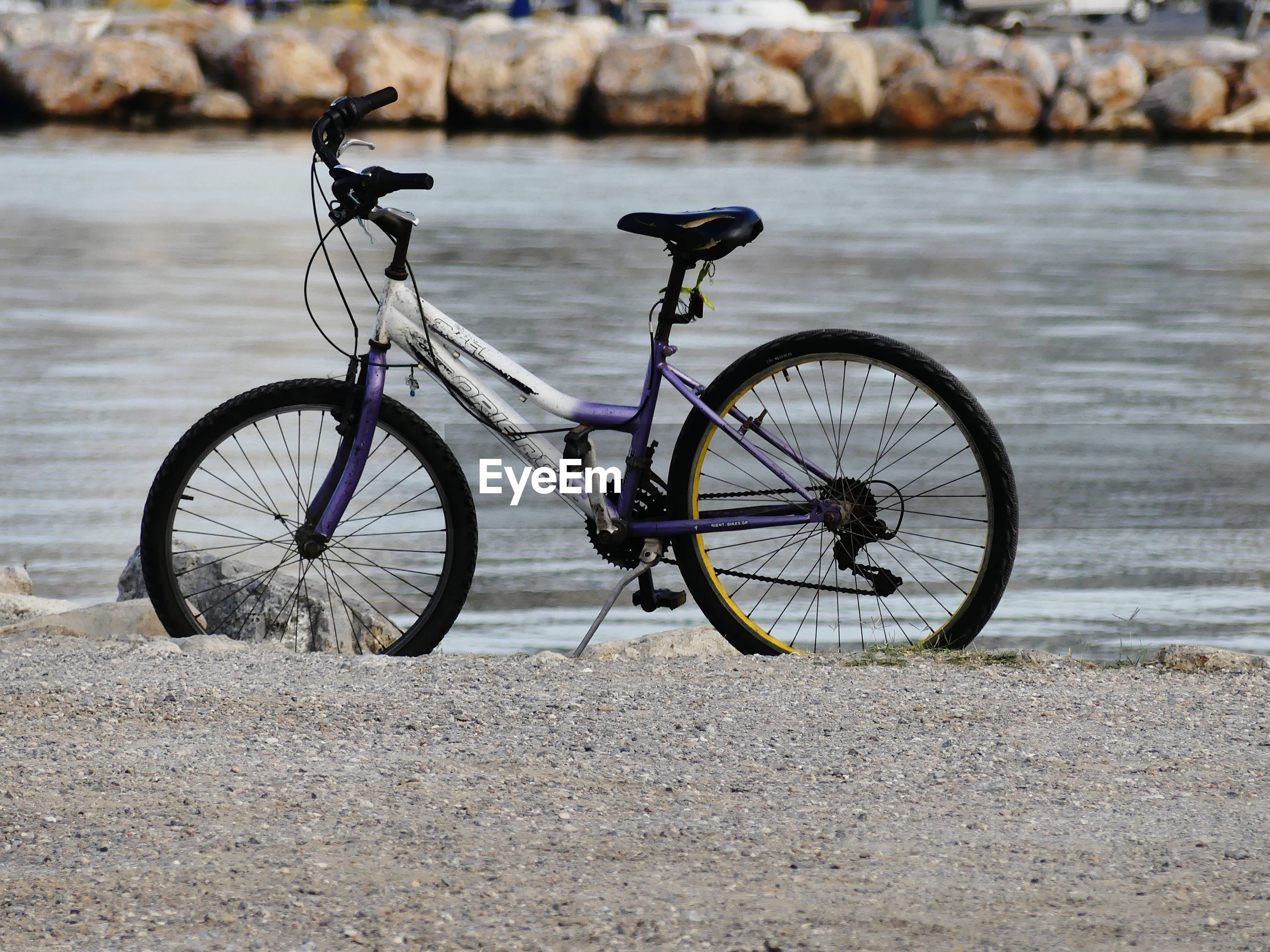 BICYCLE PARKED ON RIVERBANK