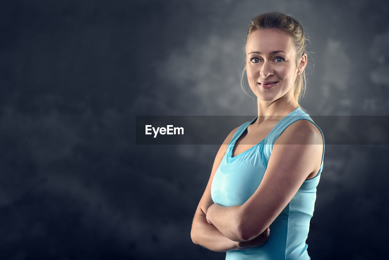 sports clothing, looking at camera, young adult, sport, one person, women, young women, lifestyles, exercising, healthy lifestyle, standing, portrait, waist up, clothing, indoors, beauty, adult, athlete, beautiful woman, body conscious