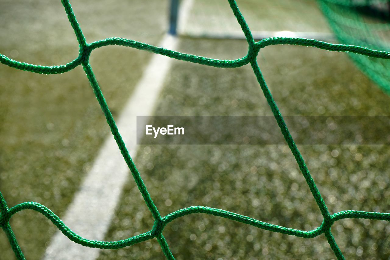 sport, green color, grass, net - sports equipment, day, pattern, close-up, no people, nature, focus on foreground, full frame, selective focus, soccer, backgrounds, plant, soccer field, outdoors, team sport, playing field, absence, garden hose
