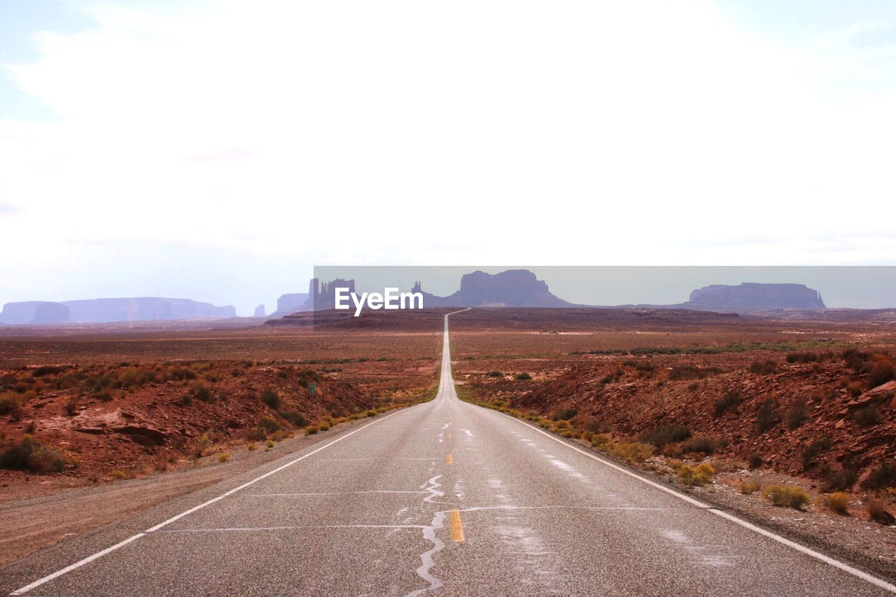 Empty Road On Landscape Against Clear Sky At Monument Valley