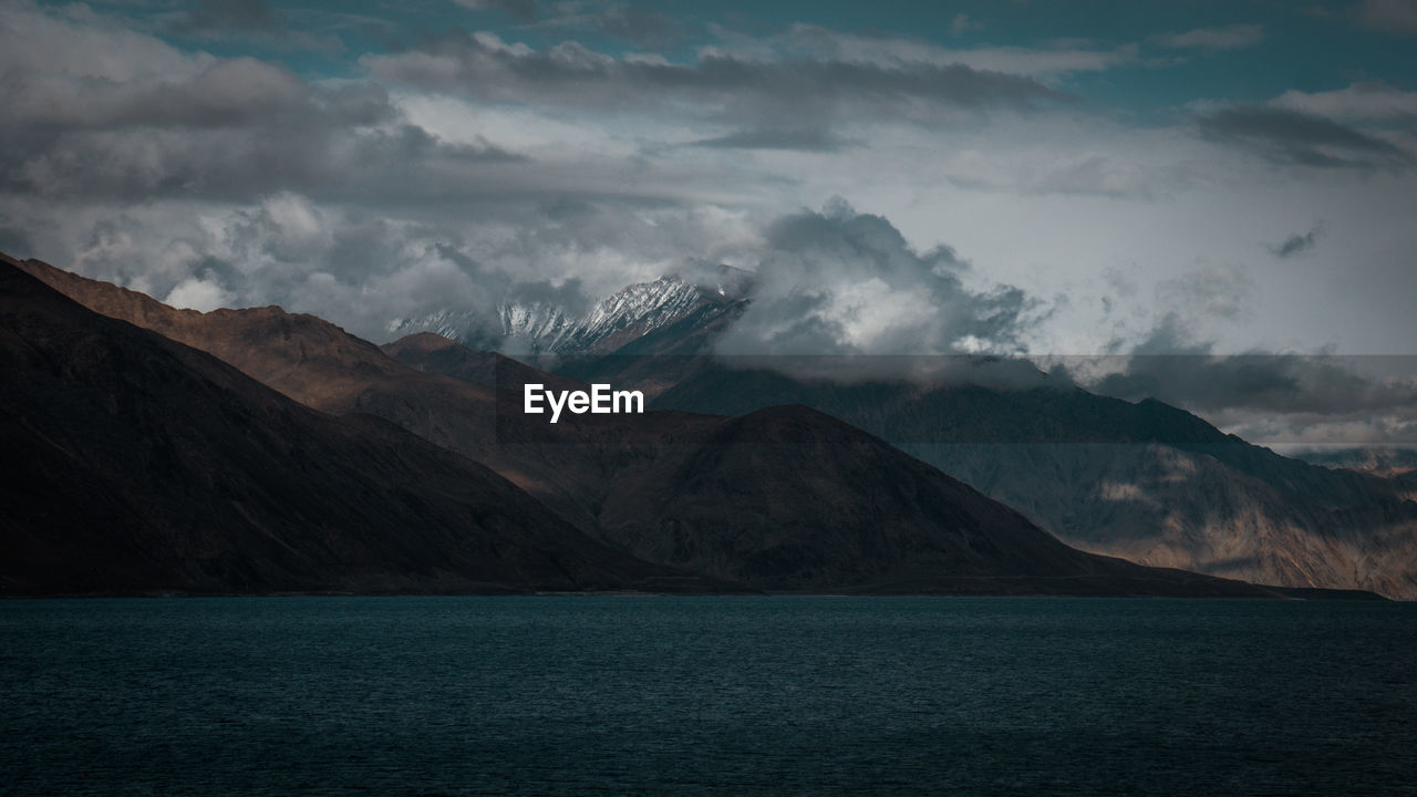 Scenic view of sea by mountains against sky