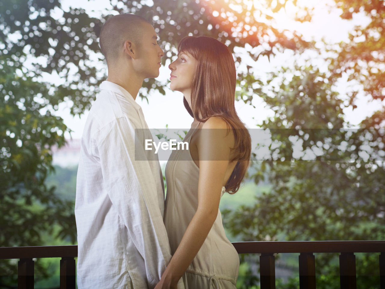 Side View Of Couple Standing By Railing In Balcony