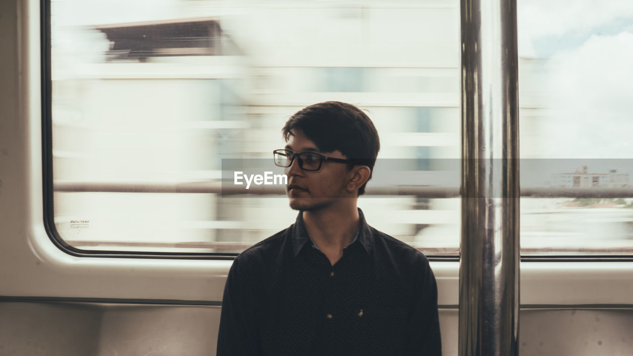 Young man looking away while sitting in train