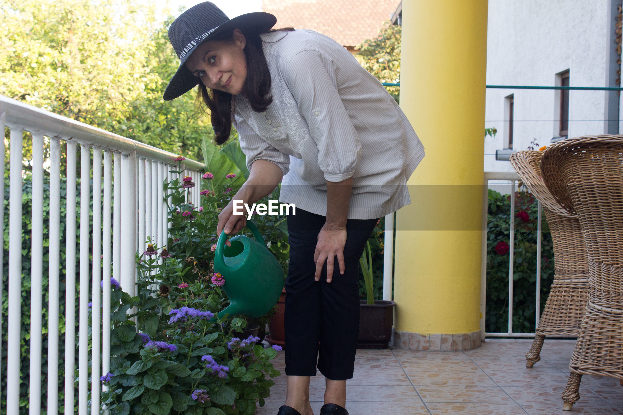 Portrait of woman watering plants while standing by railing