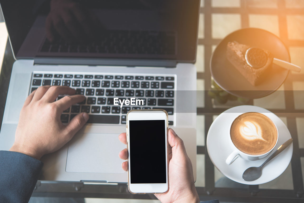wireless technology, technology, communication, connection, laptop, computer, drink, cup, mug, table, portable information device, coffee, coffee cup, food and drink, human hand, coffee - drink, refreshment, mobile phone, hand, indoors, using laptop, keyboard, frothy drink, crockery