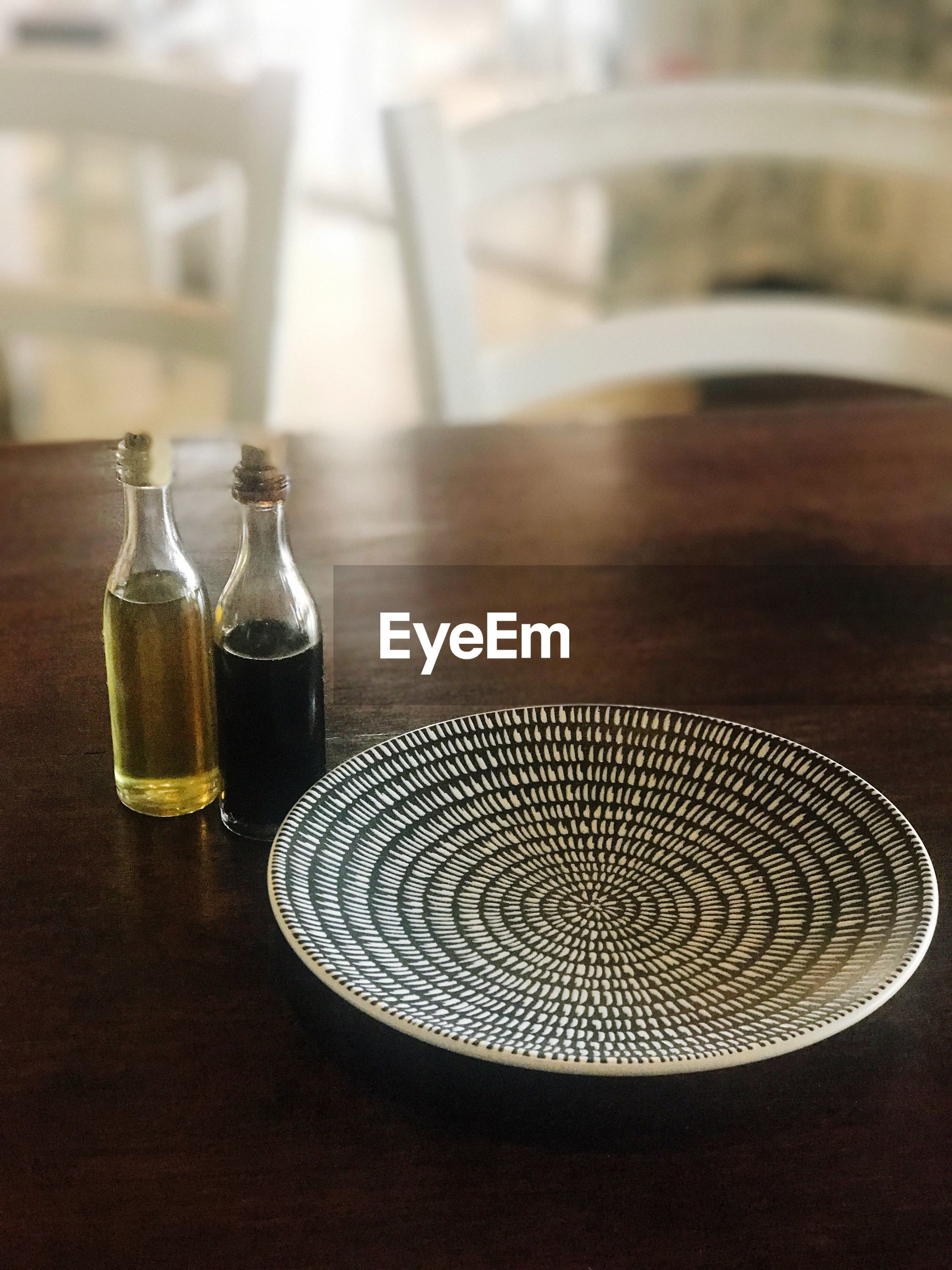 Bottles with plate on wooden table