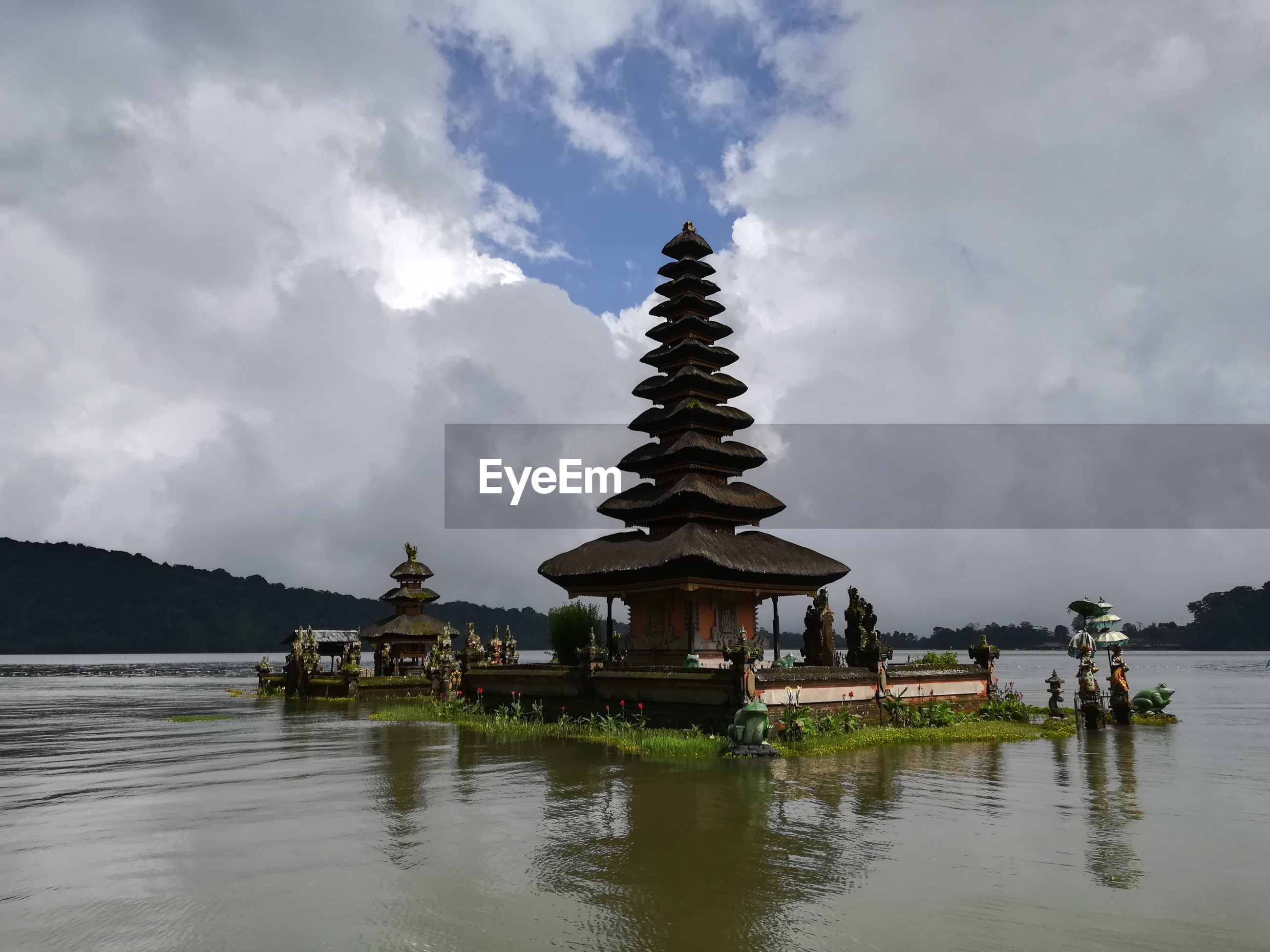 View of temple over lake against cloudy sky