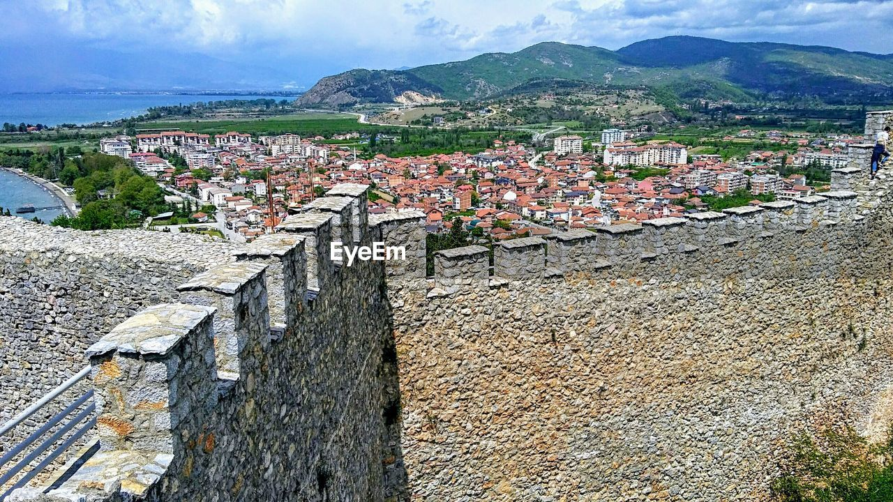 architecture, built structure, building exterior, mountain, city, residential district, building, day, nature, sky, wall, town, no people, roof, history, house, high angle view, the past, outdoors, cityscape, townscape, stone wall