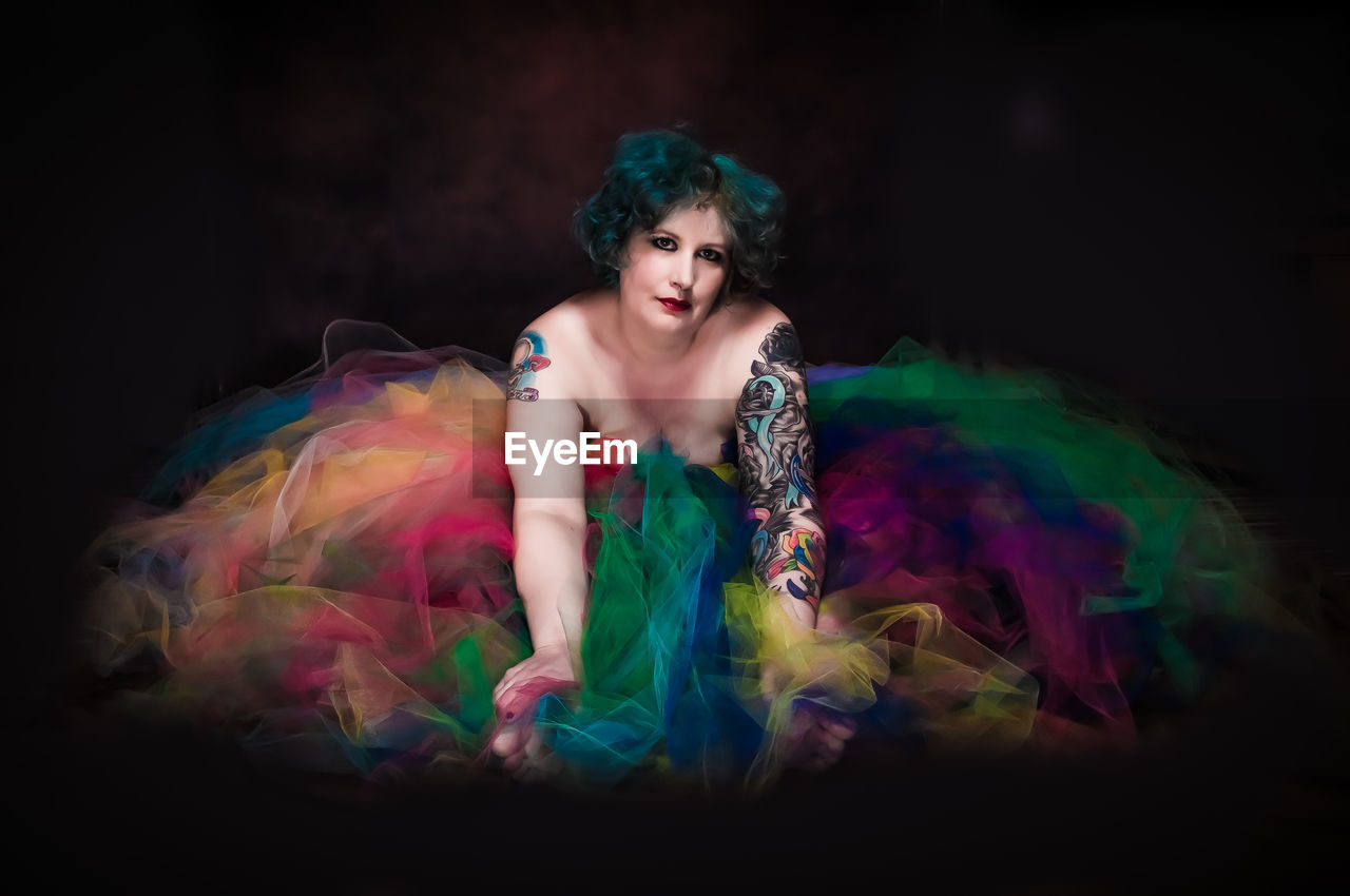 Portrait Of Woman With Tattoo Amidst Tulle Netting Against Black Background