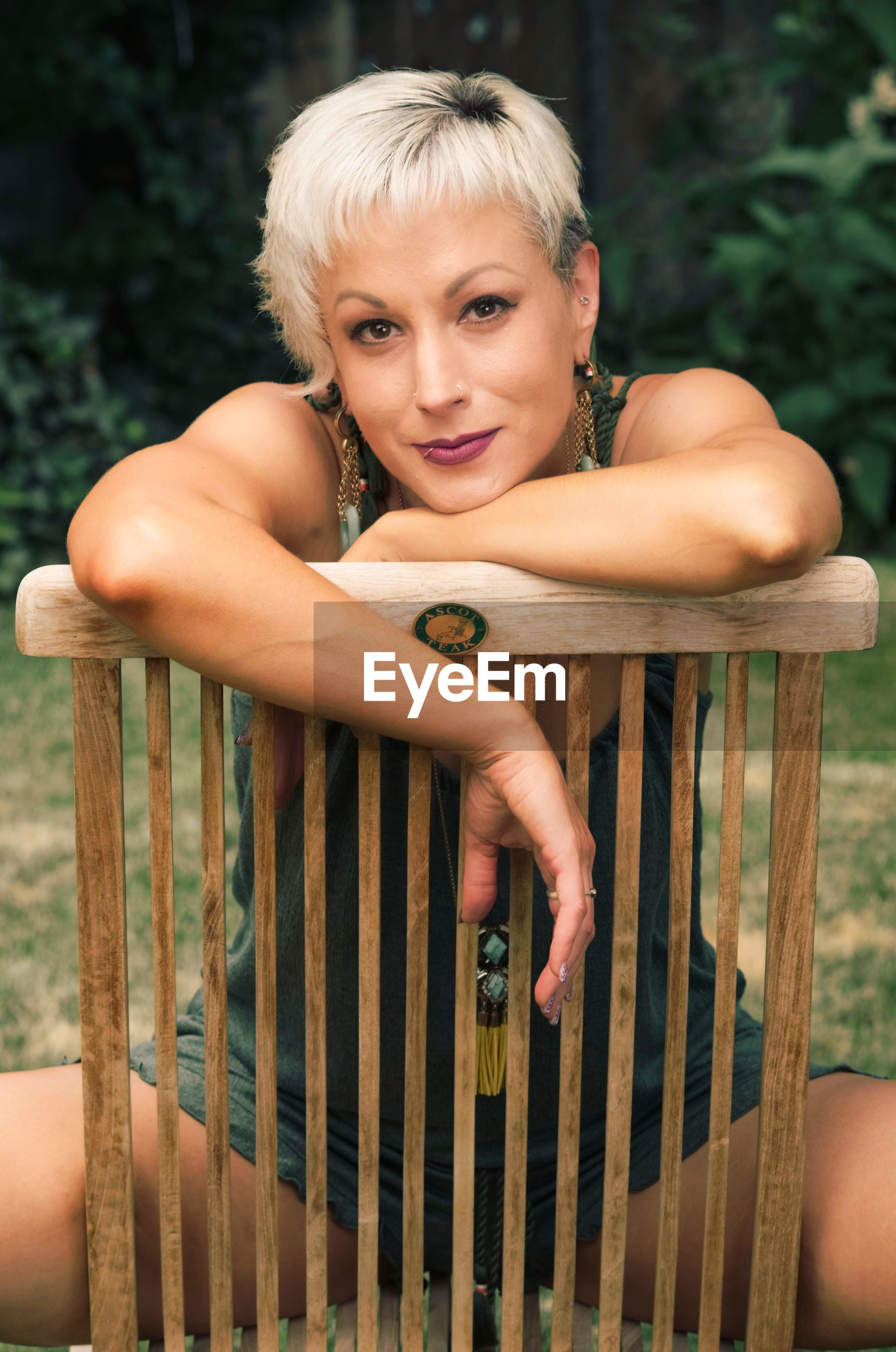 looking at camera, portrait, real people, one person, lifestyles, leisure activity, young adult, sitting, young women, front view, women, adult, beautiful woman, chair, seat, wood - material, blond hair, hair, hairstyle