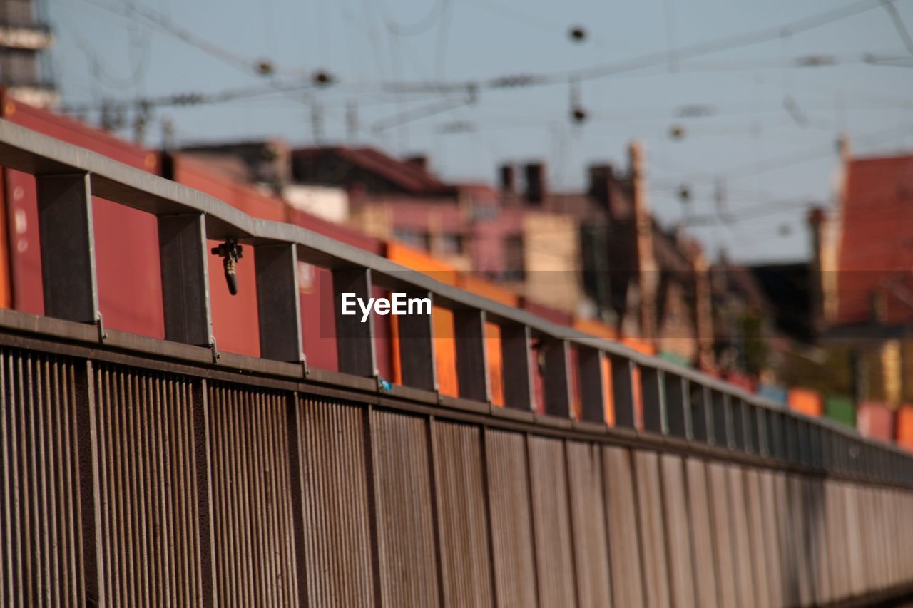 built structure, architecture, building exterior, focus on foreground, selective focus, railing, day, building, connection, nature, no people, outdoors, metal, transportation, sky, safety, city, close-up, protection