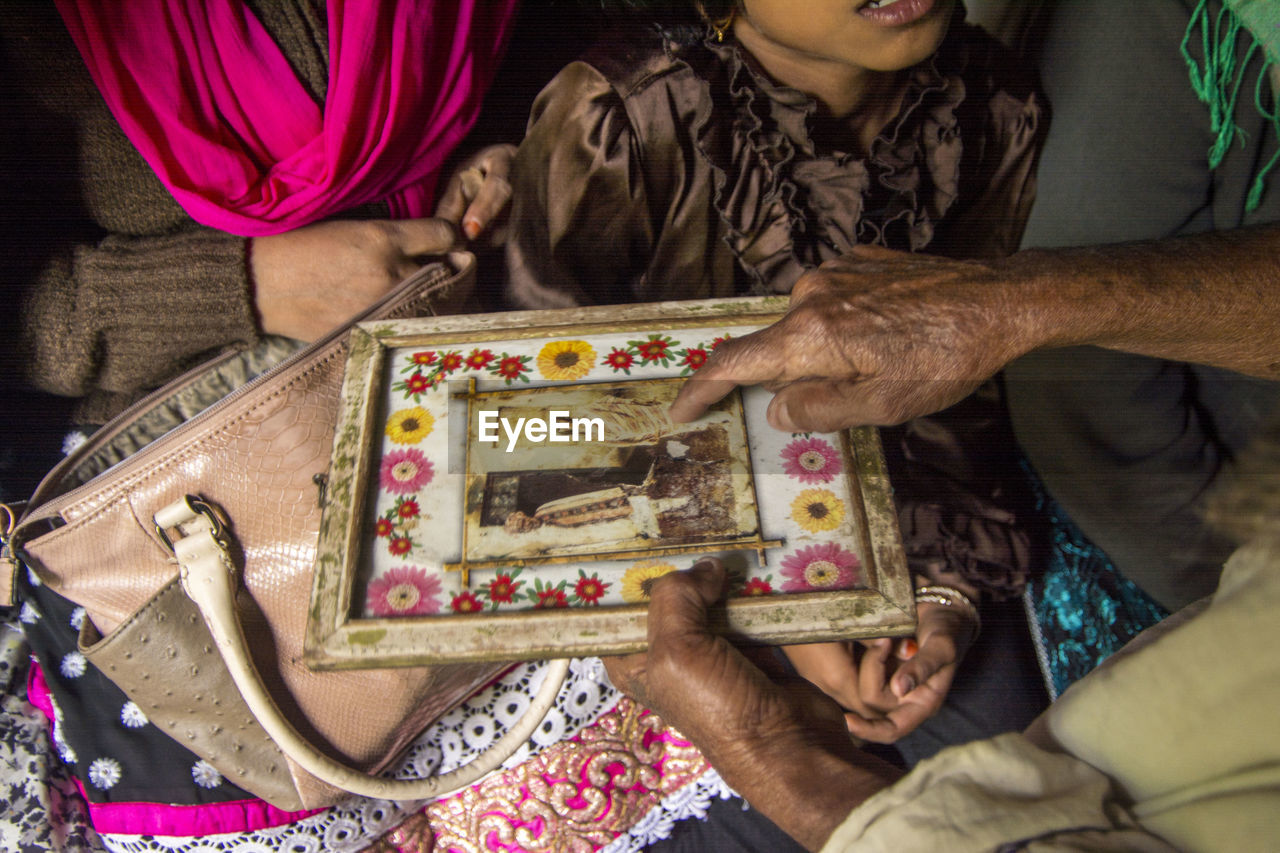 Cropped man showing old photograph to woman and her daughter