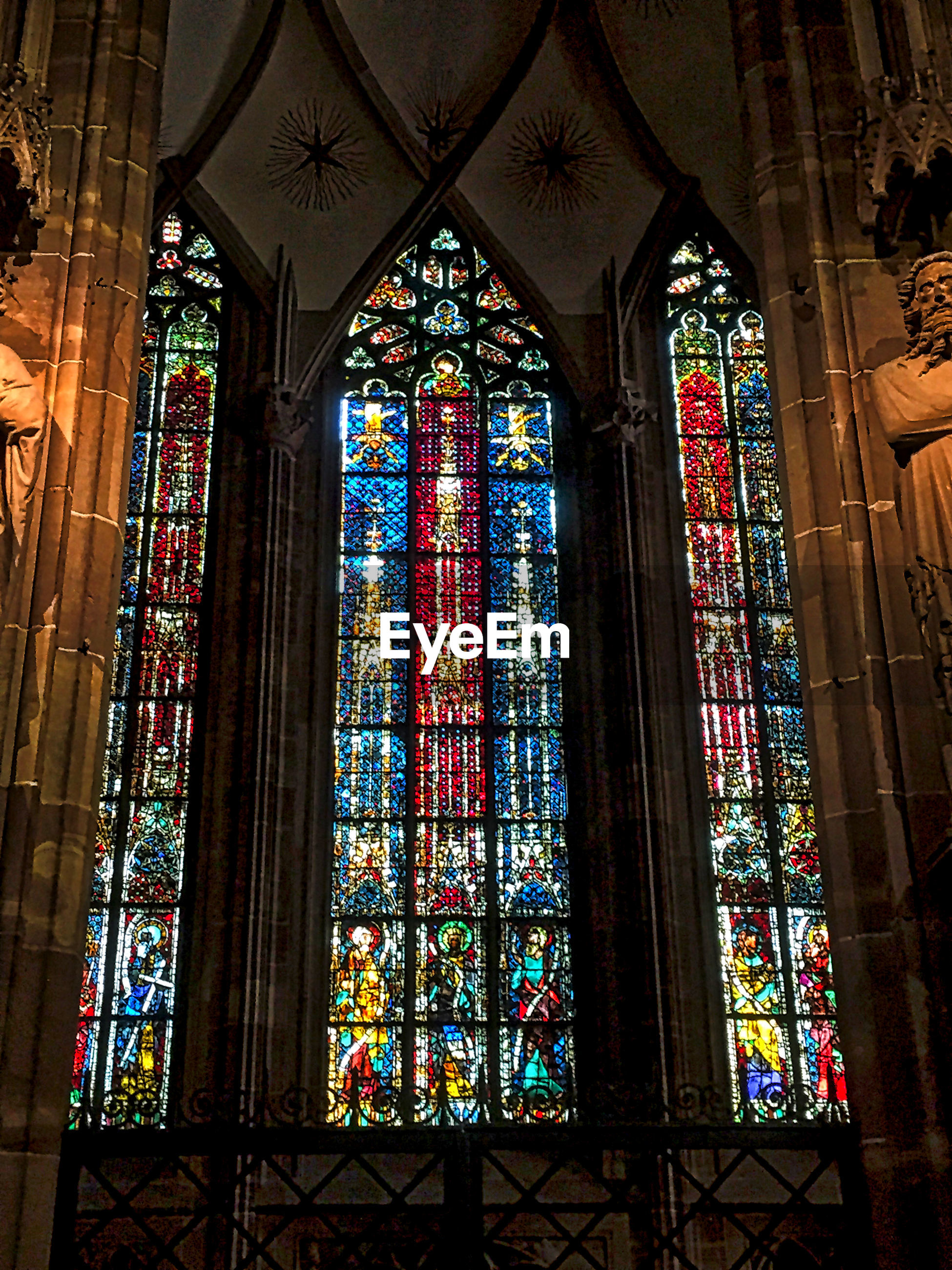window, stained glass, multi colored, indoors, religion, spirituality, low angle view, art, place of worship, church, art and craft, ceiling, glass - material, colorful, glass, multicolored, architectural column, tranquility, art product, architecture and art, creativity, red color