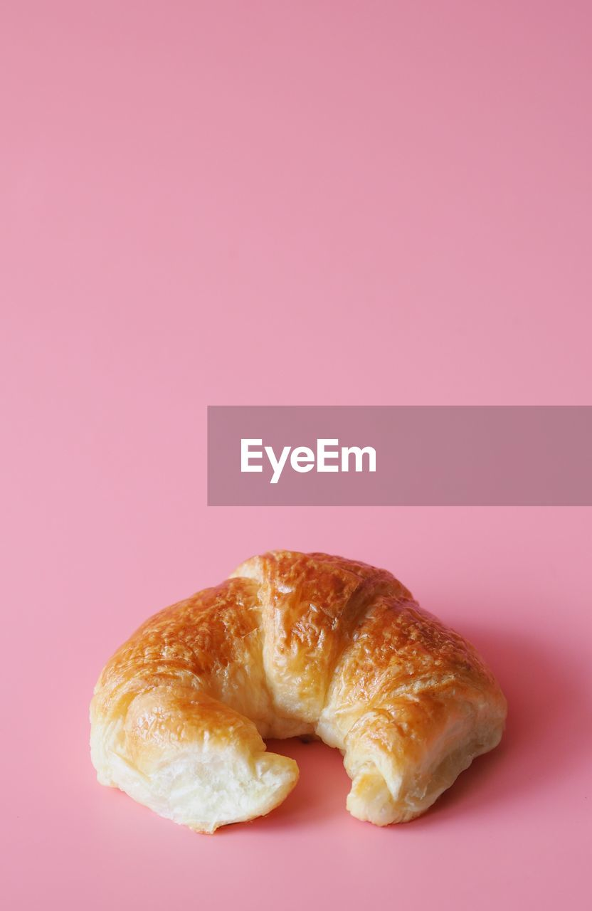 High Angle View Of Croissant Over Pink Background