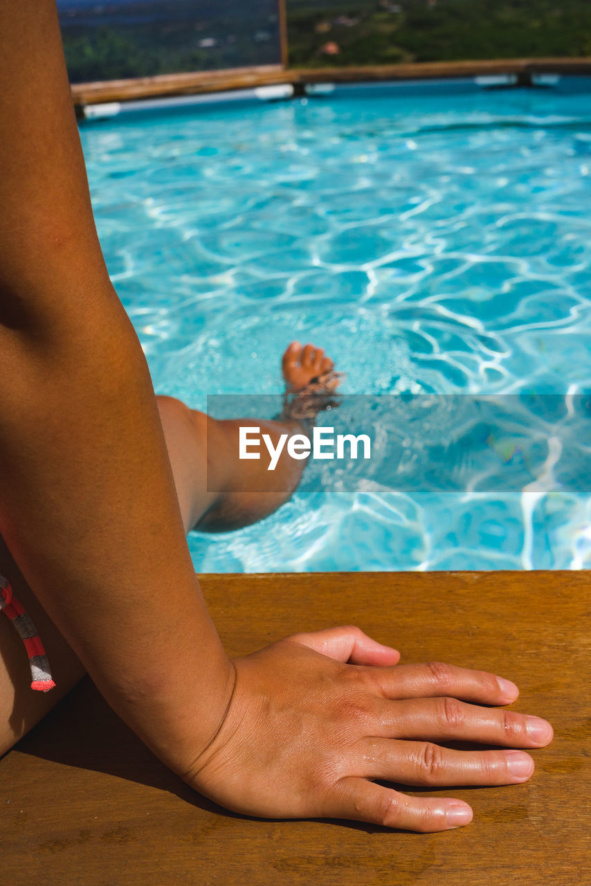 water, pool, swimming pool, real people, one person, lifestyles, leisure activity, human leg, human body part, poolside, day, body part, nature, low section, adult, women, relaxation, barefoot, hand, human foot, human limb