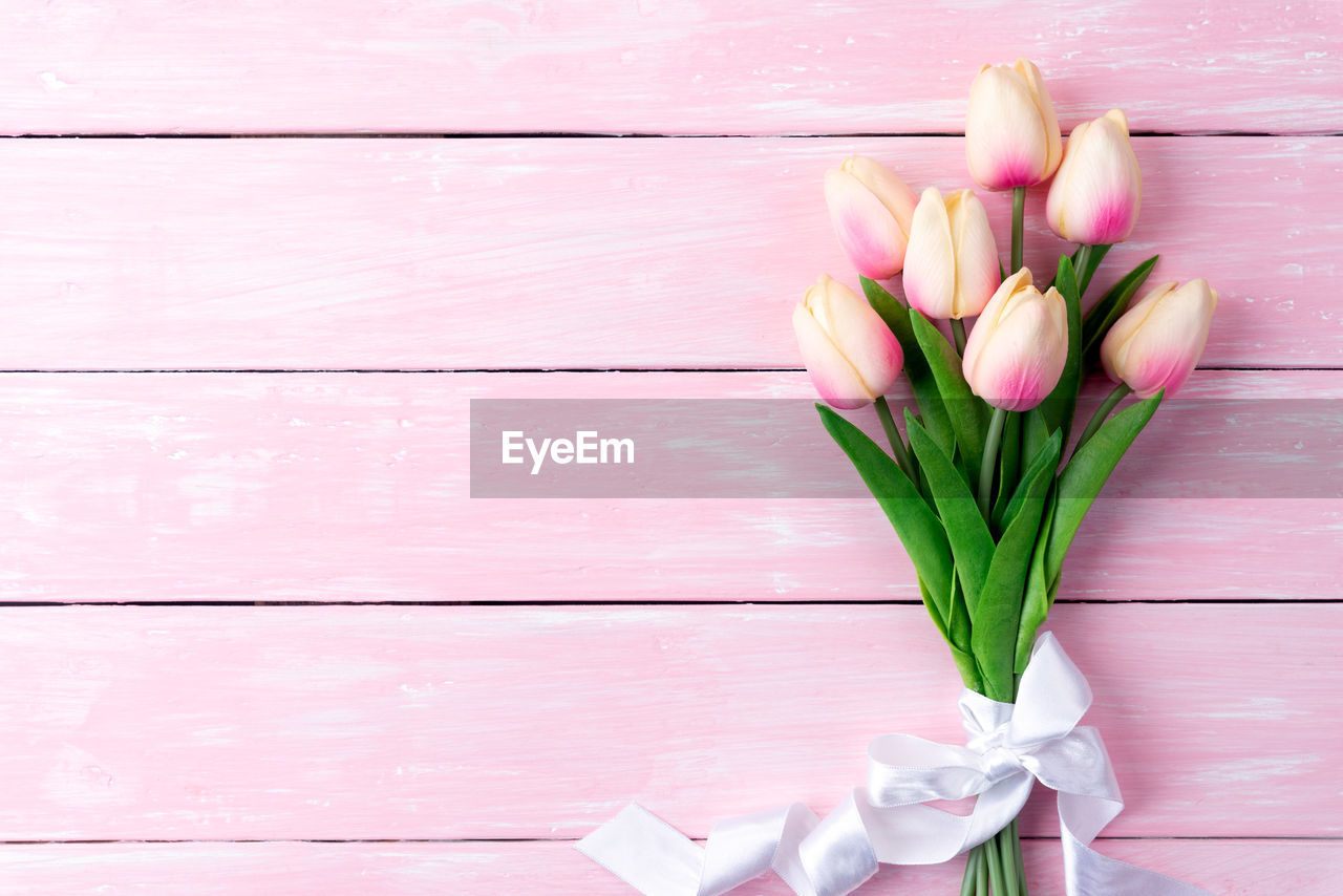 flower, flowering plant, plant, freshness, wood - material, beauty in nature, petal, vulnerability, fragility, pink color, tulip, nature, close-up, no people, inflorescence, indoors, flower head, table, directly above, flower arrangement