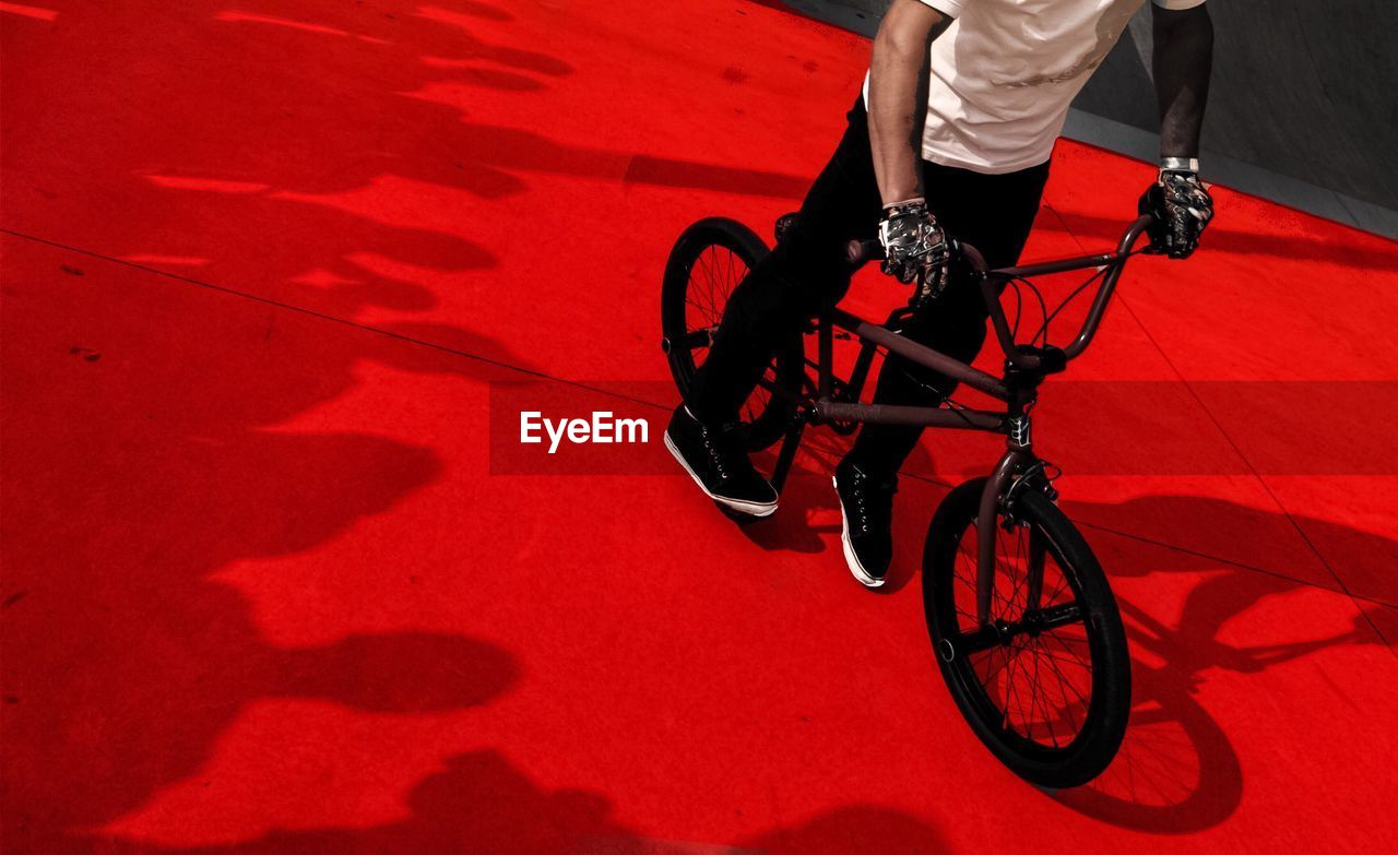 Low Section Of Man Riding Bicycle On Red Surface