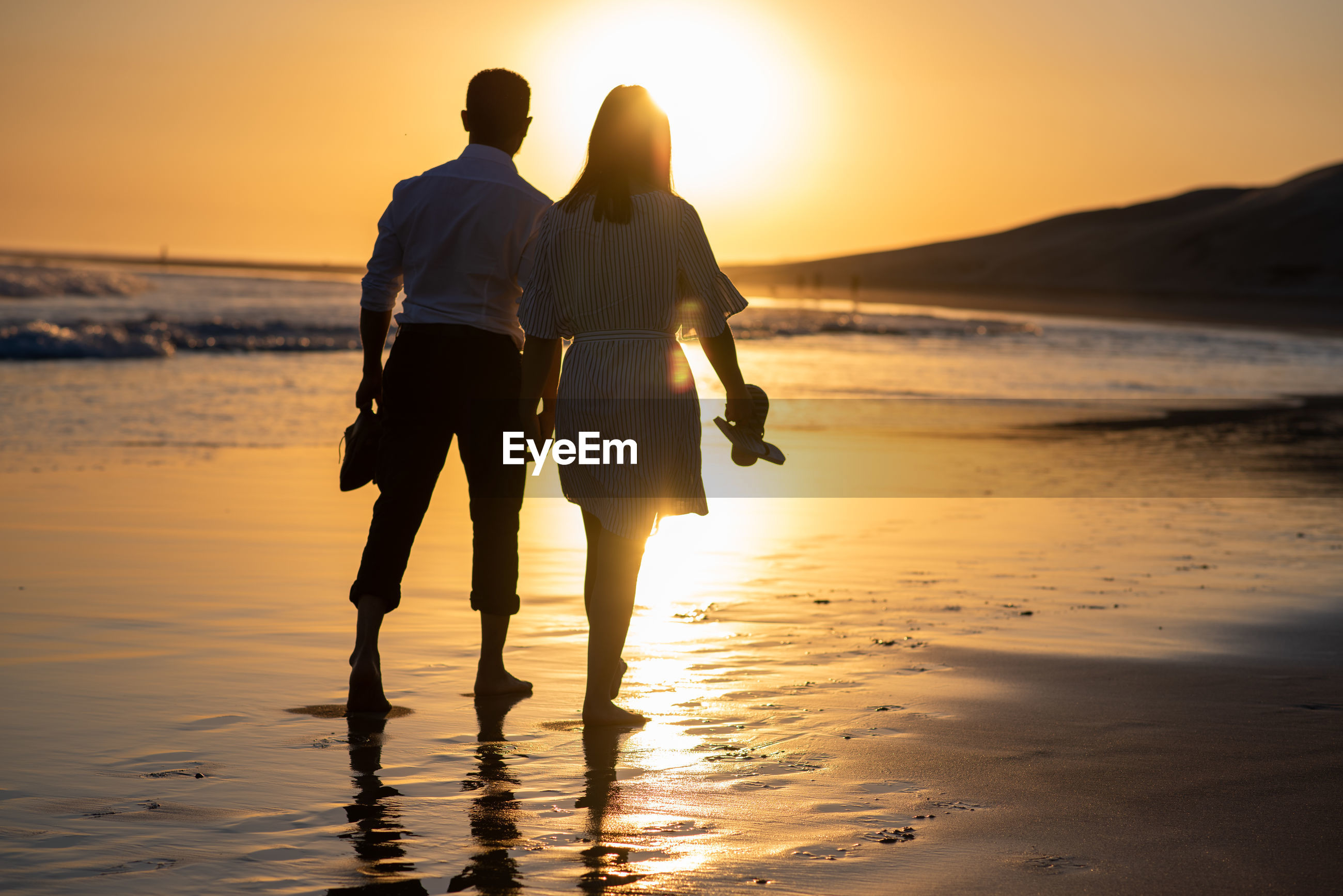 Couple holding hands while walking at beach against sky during sunset