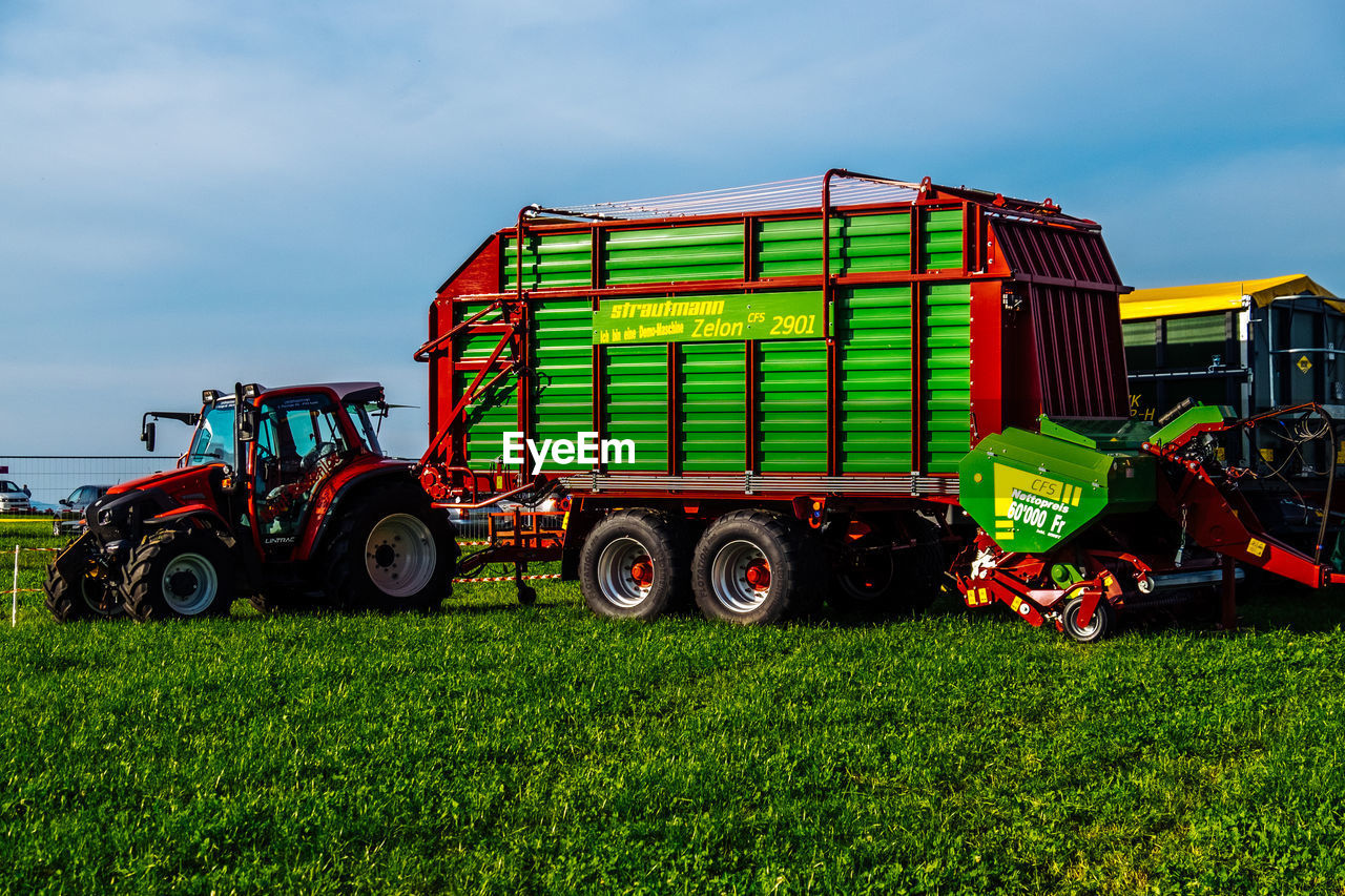 land vehicle, transportation, green color, sky, freight transportation, mode of transport, day, field, no people, outdoors, agriculture, cloud - sky, grass, industry