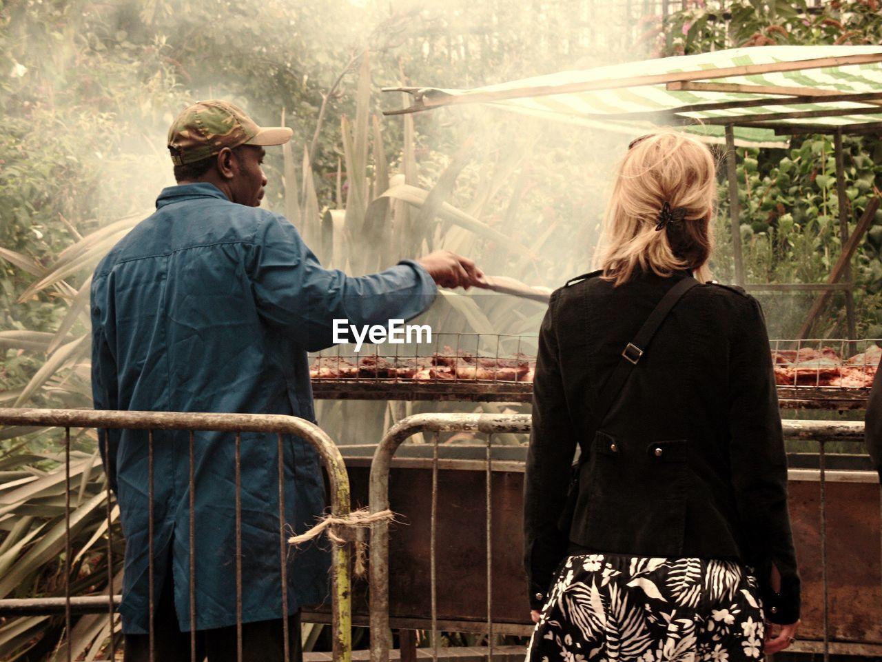 Rear View Of Woman Standing By Man Preparing Street Food