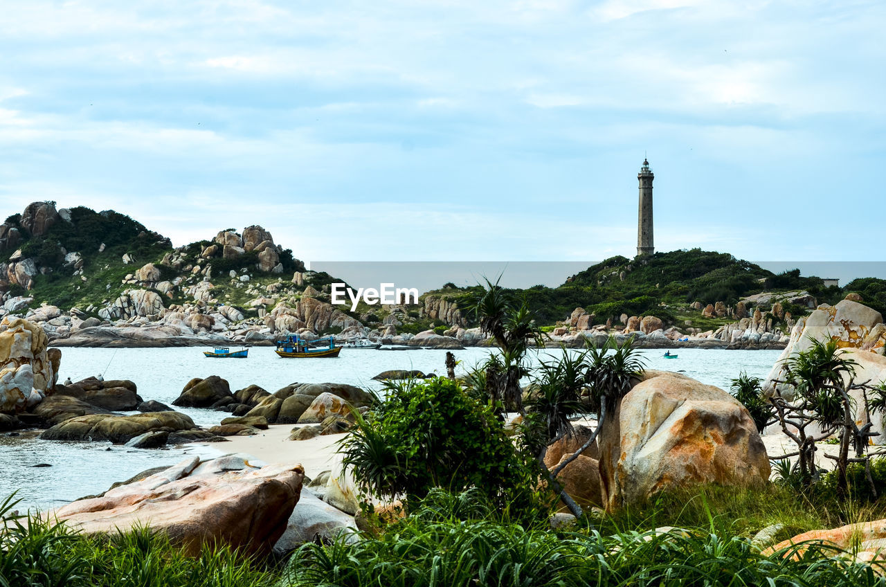 water, sky, architecture, built structure, cloud - sky, rock, nature, plant, rock - object, solid, building exterior, day, no people, beauty in nature, building, grass, tower, tree, sea, lighthouse, outdoors