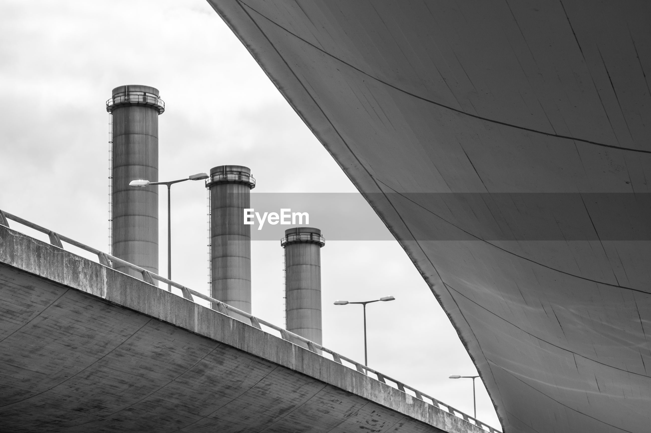 Low angle view of storage tanks on bridge against sky