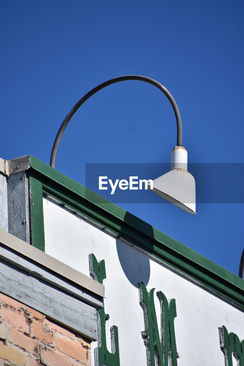low angle view, architecture, sky, blue, built structure, lighting equipment, building exterior, street light, no people, nature, clear sky, day, street, building, metal, outdoors, light, copy space, electric light, sunlight, light fixture, electric lamp
