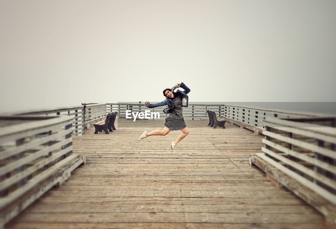 Woman jumping on pier against clear sky