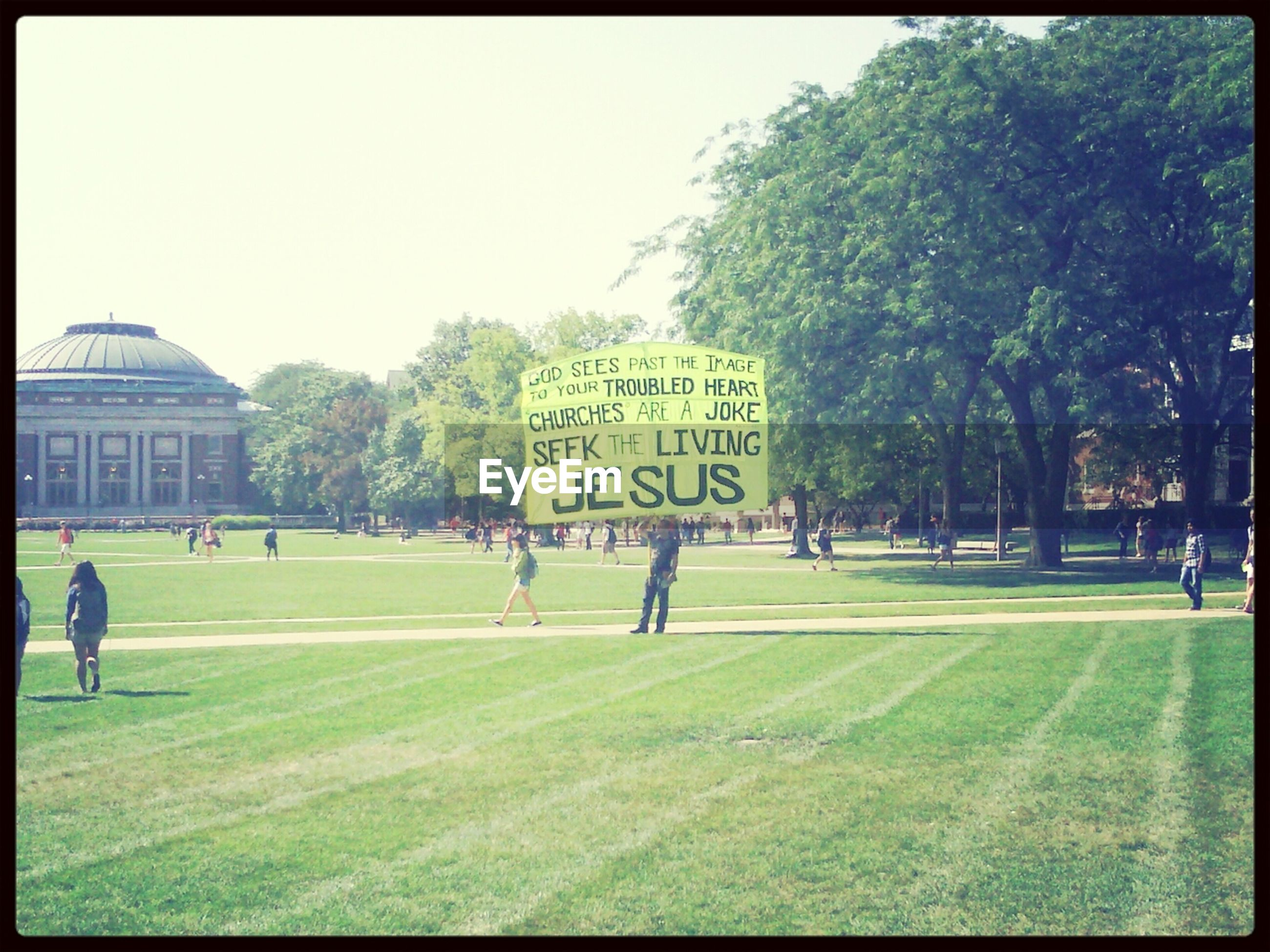 grass, transfer print, tree, text, western script, building exterior, built structure, architecture, auto post production filter, green color, clear sky, communication, field, incidental people, large group of people, day, lawn, outdoors, grassy, sky