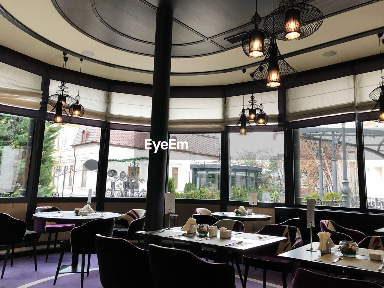 table, indoors, lighting equipment, window, restaurant, no people, business, food and drink, day, glass - material, pendant light, hanging, ceiling, furniture, light bulb, transparent, large group of objects, absence, seat, electric lamp, crockery