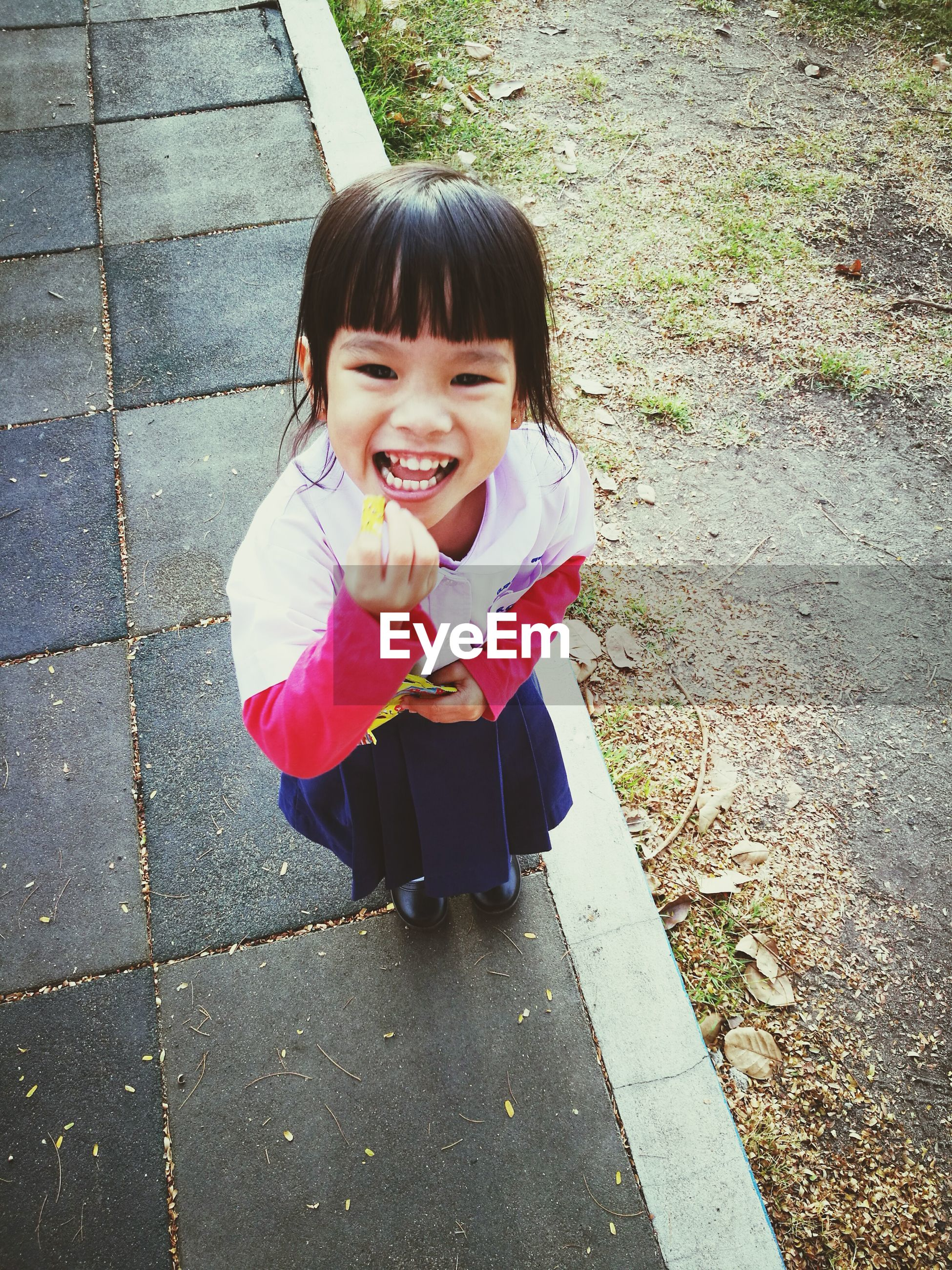 childhood, high angle view, innocence, real people, child, outdoors, bangs, cute, full length, girls, one person, looking at camera, portrait, happiness, smiling, day, cheerful, people