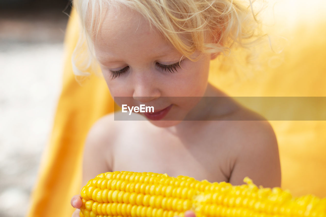 Blond and curly toddler girl eating corn on the beach. yellow colors, summer mood