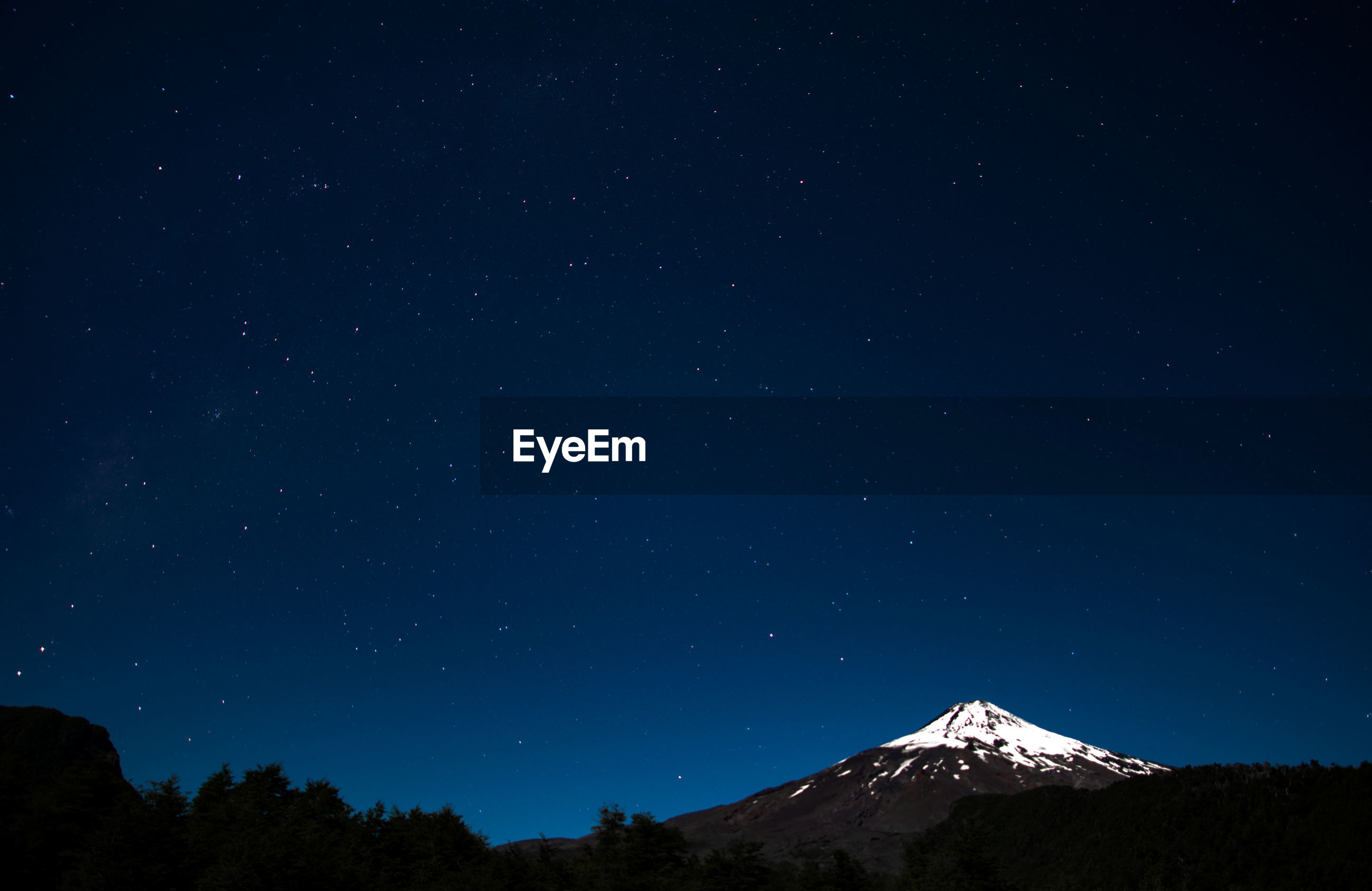 Low angle scenic view of star field over mountain against blue sky during winter