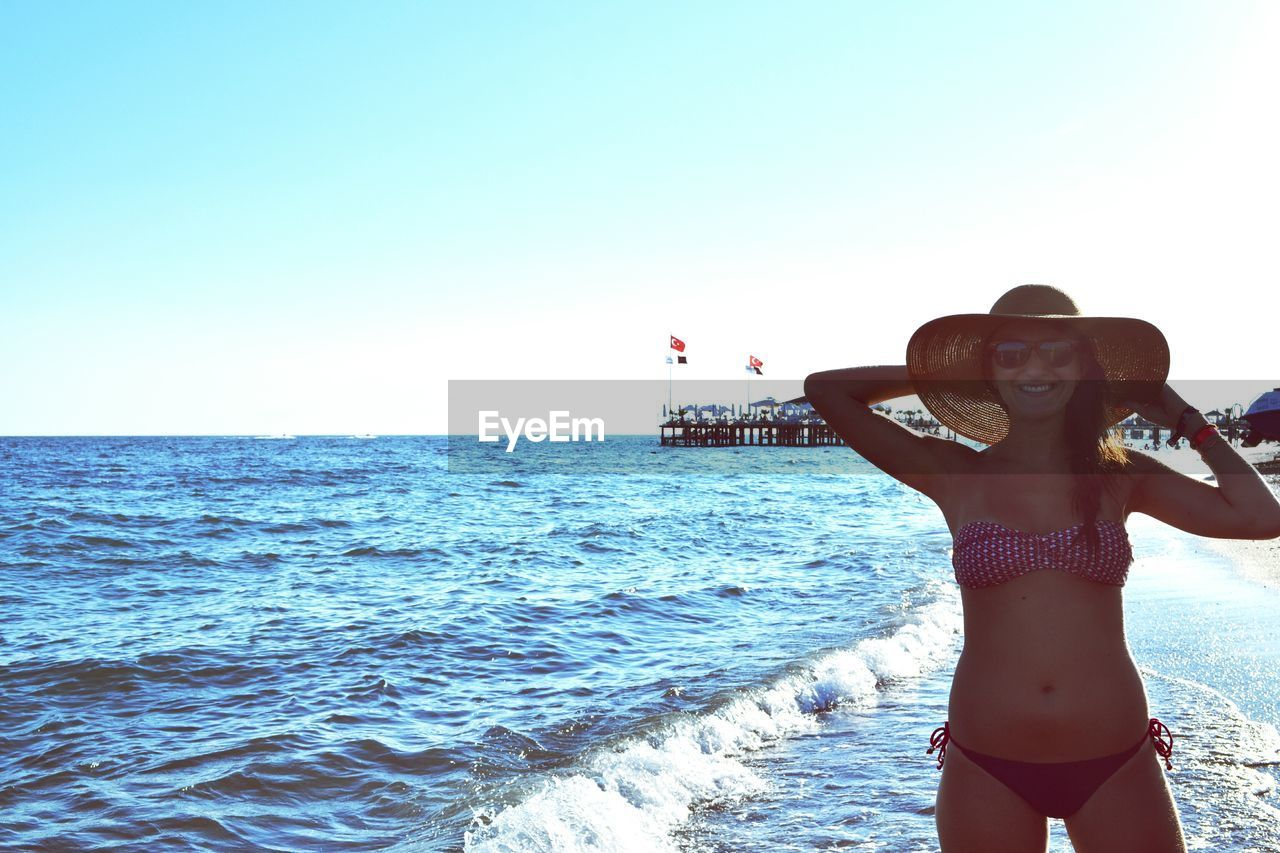 sea, bikini, three quarter length, horizon over water, beauty in nature, real people, leisure activity, beach, one person, clear sky, water, nature, lifestyles, scenics, sunlight, outdoors, young adult, young women, vacations, summer, sky, day, standing, beautiful woman