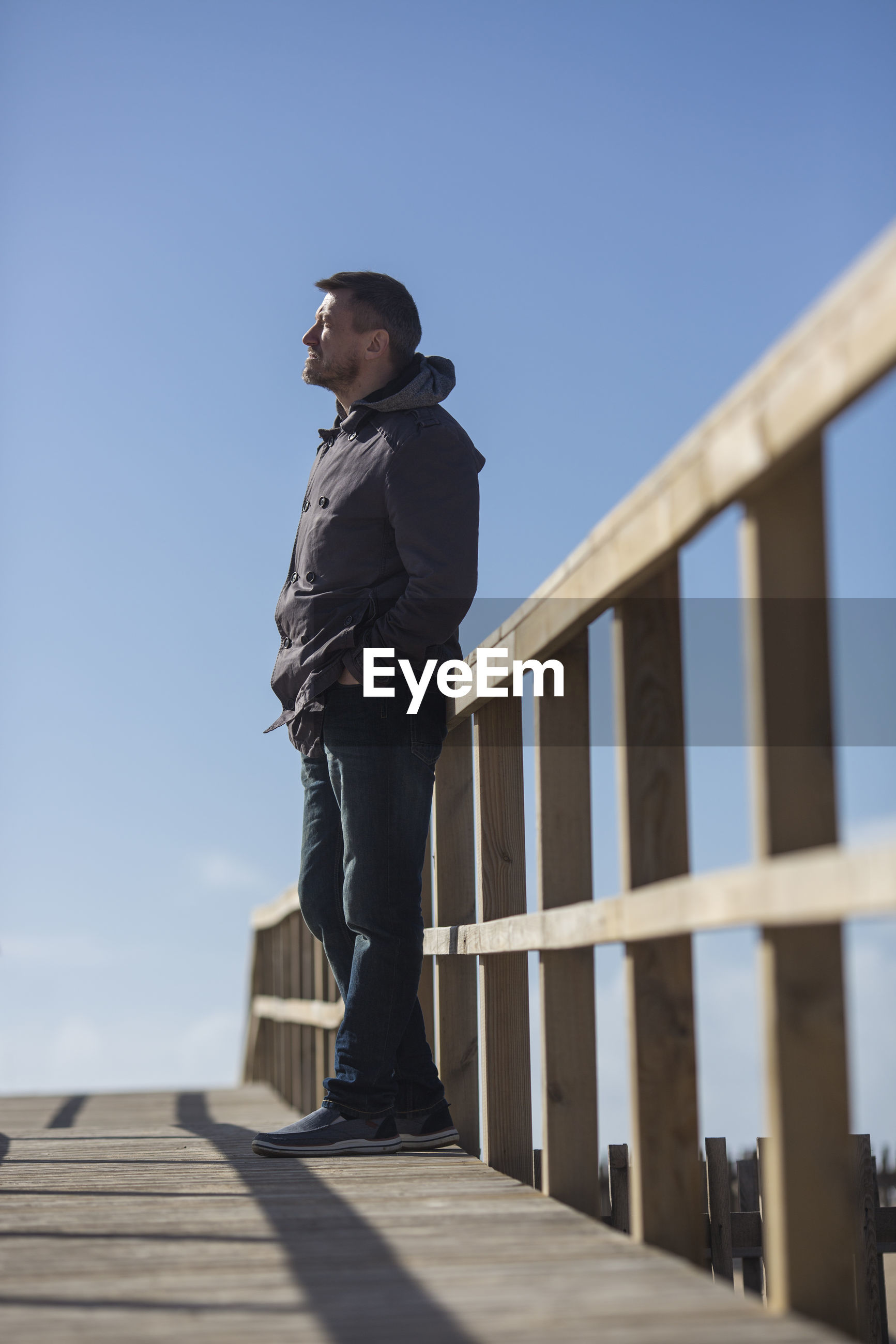Full length side view of mature man standing on footbridge against clear blue sky