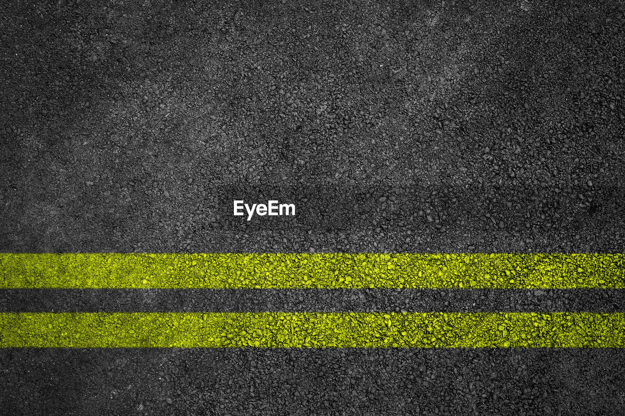 sign, striped, no people, full frame, green color, textured, asphalt, single line, backgrounds, dark, road, black color, pattern, transportation, grass, road marking, communication, yellow, outdoors, rough, textured effect