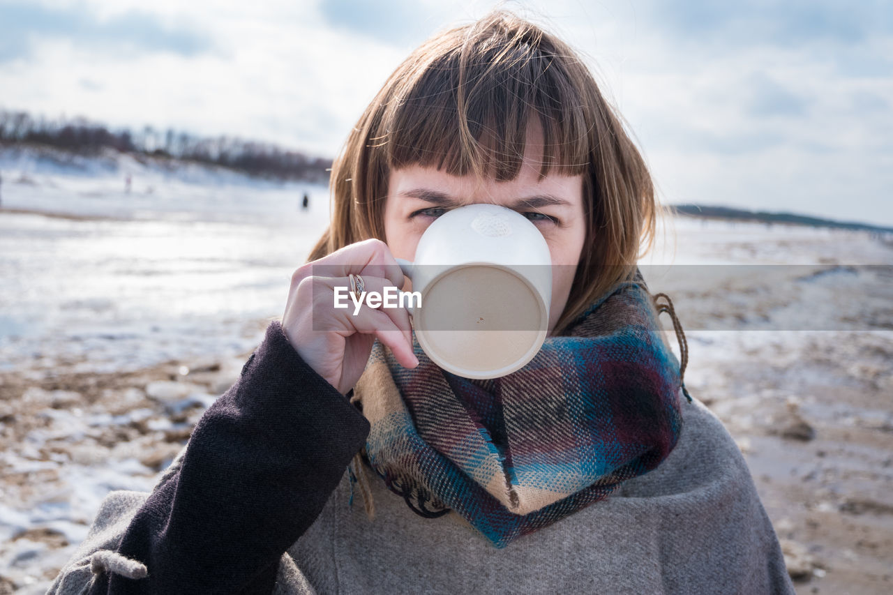 Close-Up Portrait Of Young Woman Drinking Coffee At Beach