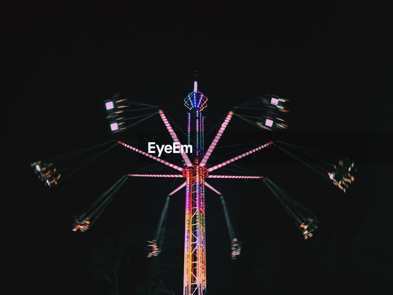 Low Angle View Of People Enjoying Illuminated Chain Swing Ride Against Sky At Night