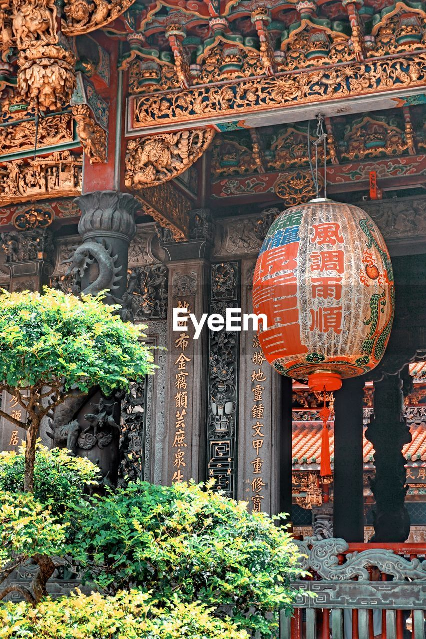 architecture, built structure, building, religion, no people, belief, place of worship, day, spirituality, text, plant, non-western script, script, lantern, communication, nature, decoration, outdoors, architectural column, ornate, chinese lantern