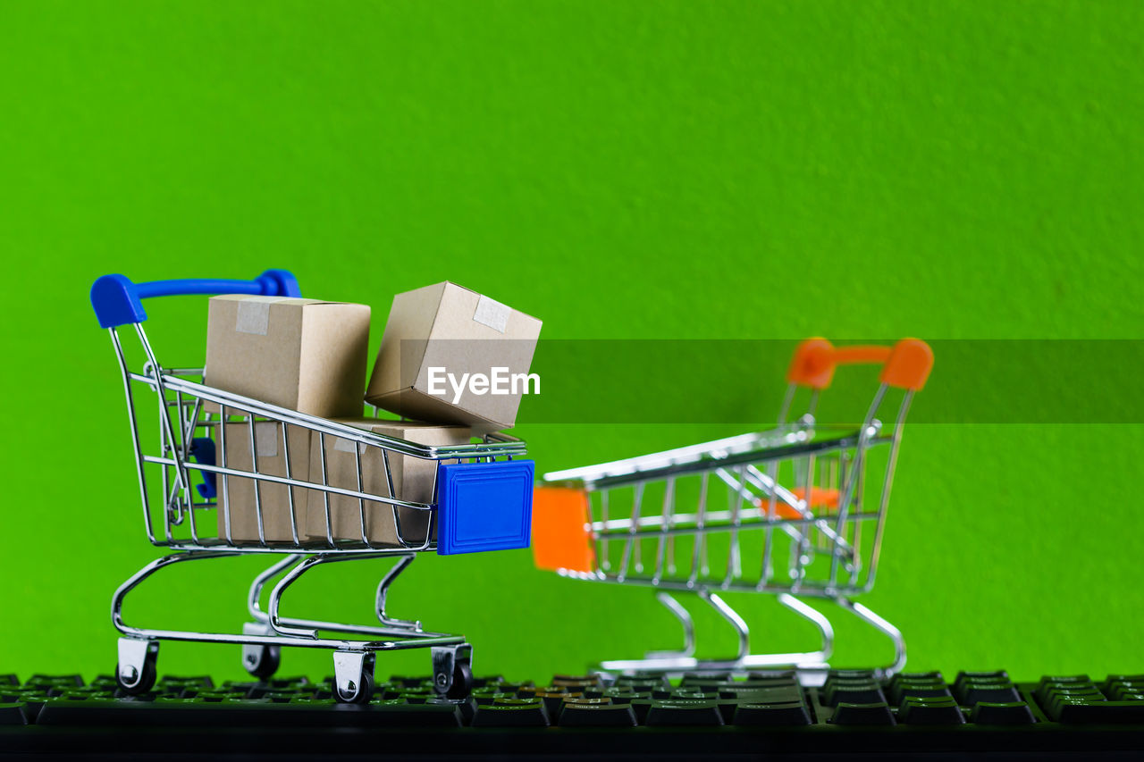 Shopping cart on computer keyboard against green background