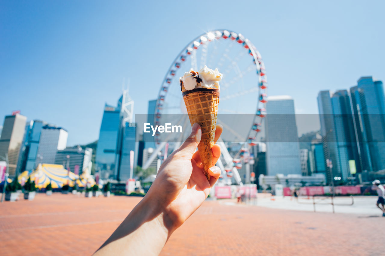 Cropped Image Of Hand Holding Ice Cream Against Ferris Wheel In City