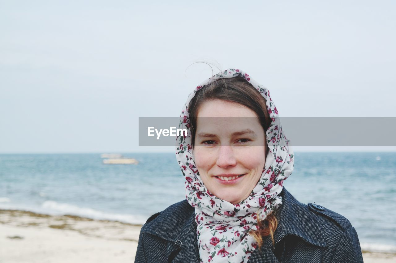 Portrait Of Smiling Young Woman Against Sea