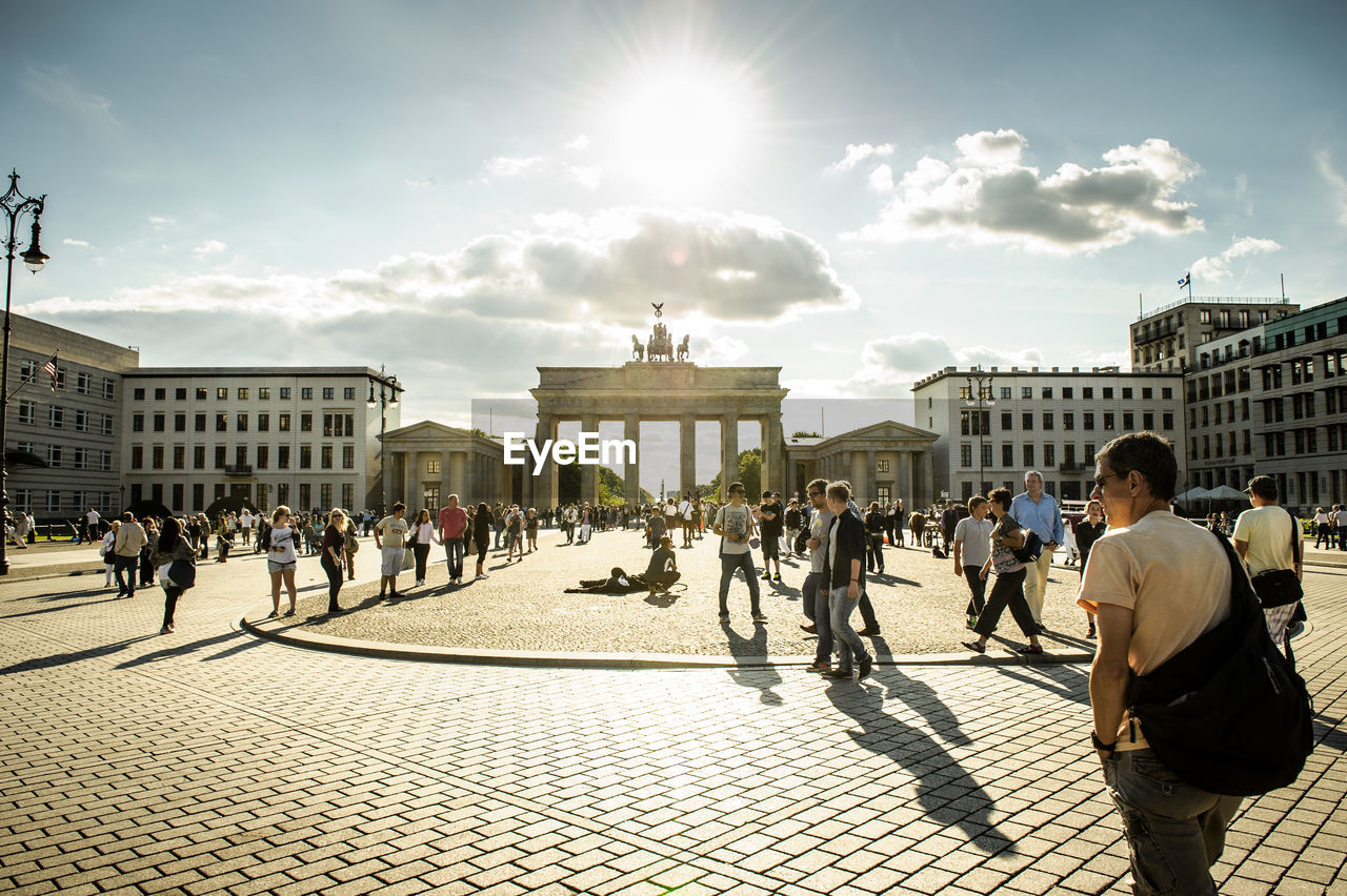 architecture, built structure, building exterior, tourism, sunlight, travel destinations, real people, travel, large group of people, town square, sky, history, city, sun, men, outdoors, women, day, people, adult